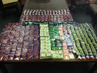 Police displays synthetic marijuana and cash found as a result of an investigation.