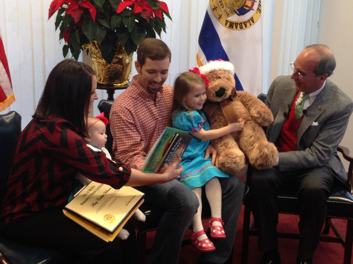 Mary Carlisle Williams accepts a teddy bear from Mayor Sandy Stimpson with her mother Mandy, her father Andrew and sister Molly. A video of Mary Carlisle went viral after she said she'd rather go to Mobile than Disney World.