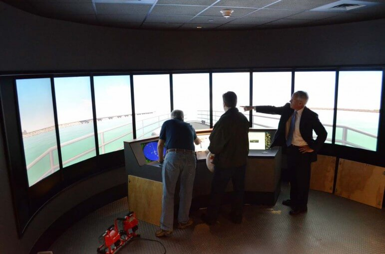 LAGNIAPPE | GulfQuest Executive Director Tony Zodrow (right) demonstrates a pilot boat simulator as exhibits were being installed in April 2014.