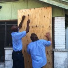 City workers place plywood over the entrance to a residence at 1303 Juniper St.