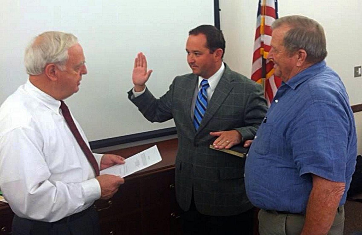 Baldwin County Commissioner Chris Elliott takes the oath from Baldwin County Probate Judge Tim Russell days after defeating incumbent Bob James in a GOP runoff.