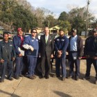 Mayor Sandy Stimpson, center, poses for a photo with employees Lee Bush, Clarence Mack, Tyrone Holley, Mayor Stimpson, James Gardner, Larry Harris and Jamaal Hawthorn behind a trailer the city garage workers built to save the city money. Stimpson gave the employees a $250 bonus for the work.