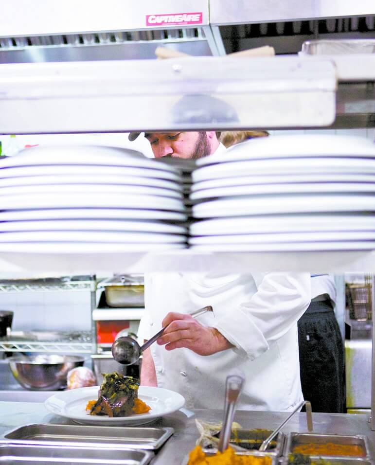 Chef Mike Devaney plates dishes at The Bull, a 6-year-old fine dining restaurant downtown.