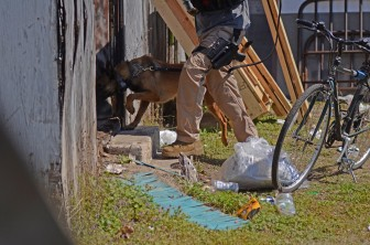 A K-9 unit searches a property on State Street that was the focus of a five-month, multi-agency drug investigation on Feb. 27.