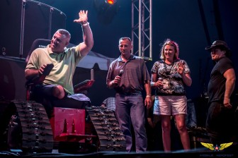 """The Independence Fund presents retired U.S. Army Sgt. Dustin Tuller with a """"Tank"""" track chair onstage during AeroFest."""