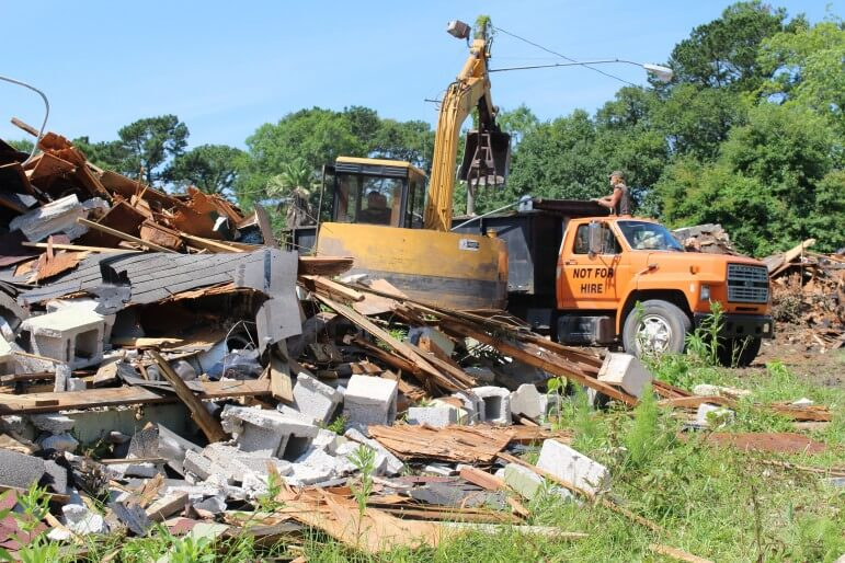 Crews work to remove debris from the former Joel Court Apartments, a $125,000 demolition of blighted property donated to a local church from its former owner, Colorado-based Legacy Capital Partners.
