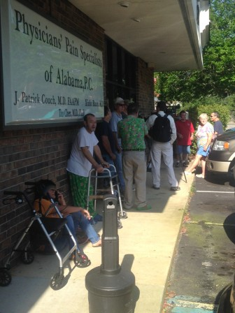 Patients wait in line outside of Physicians' Pain Specialists the day after the business proprietors, Dr. John Patrick Couch and Dr. Xiulu Ruan, were federally indicted.