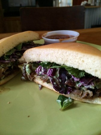 A smoked lamb shank sandwich with a mint aioli, mint, cabbage on a homemade bun from Mister John's BBQ.