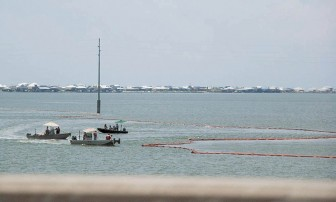 (Photo/Gabriel Tynes) Workers deploy boom near Dauphin Island during the 2010 BP Deepwater Horizon oil spill.