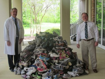 (photo/) Courtesy of Baldwin Bone & Joint) Drs. John Todd and Drew Corbett, orthopedic surgeons with Baldwin Bone & Joint, display some of 2,729 pairs of shoes collected during the 2015 Many More Miles Campaign.