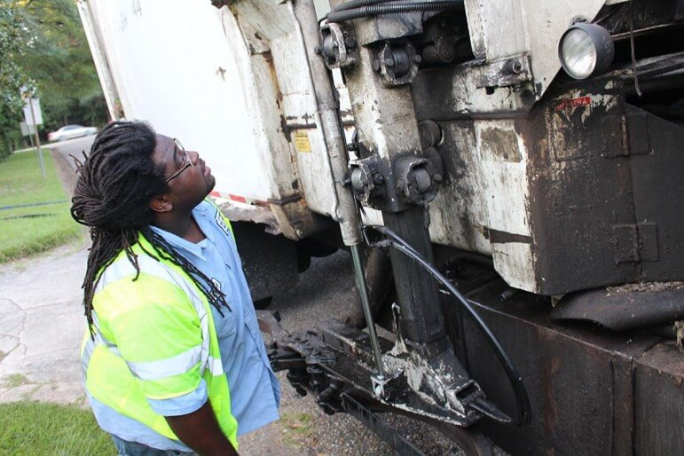 (Dale Liesch) Cortez Hunter, a driver with the city of Mobile, checks a busted hydraulic line along his trash route Monday.