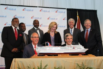 Mobile councilors Fred Richardson, from left, Levon Manzie, C.J. Small, Gina Gregory, Joel Daves and John Williams look on as Mayor Sandy Stimpson, left, and Carnival executive Terry Thornton prepare to sign a 13-month contract to make Mobile the homeport of the Fantasy.