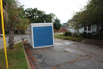 A portable storage unit sits next to a barricade on Canal Street across from property city GIS maps indicate is owned by State Rep. Adline Clarke