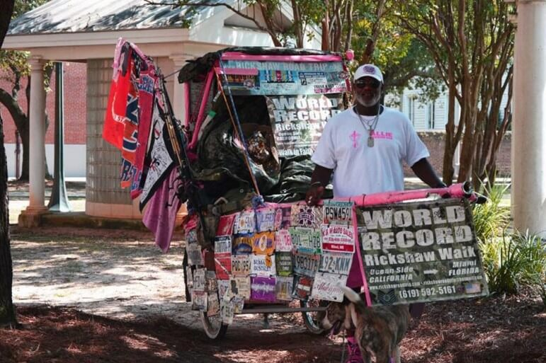 (Photo/ Holden Barnett) U.S. Marine Corp veteran Allie Stevens began walking across America with a rickshaw and a pet after he lost his wife and daughter to cancer. He's currently in Mobile County, en route to Miami.
