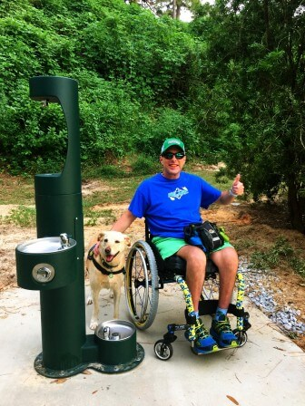 Fairhope Bike and Pedestrian Committee member Chris Riley with his dog Tonya at the new dog-and-people fountain.
