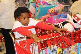 Mikell Tucker, a second grader at Whitley Elementary, pushes a cart full of toys in Target, as part of the Santa Cuz shopping spree in Mobile Thursday.