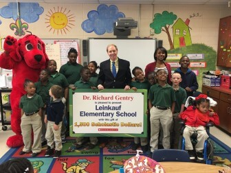Principal Dr. Quentina Pruitt, Leinkauf Elementary students, and Clifford the Big Red Dog kicked off the upcoming Scholastic Book Fair to be held March 7-11 with a gift of $1,500 presented by Dr. Richard Gentry on behalf of the Leinkauf Historic District Neighborhood Organization (LHDNO). In addition to the book fair, the neighborhood organization is raising book funds for the school with a Leinkauf Architectural Walking Tour on March 5th. The walking tour and book fair are the first of many events in March, such as the 47th Annual Historical Homes Tour, as the neighborhood and Mobile celebrate Leinkauf History Month.