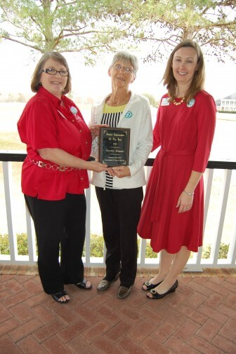 Gulf Shores & Orange Beach Tourism's Susan Brush, left, hospitality and information coordinator, and Kim Chapman, right, director of hospitality and information present Dottie Hinnant the 2016 Ambassador of the Year award at the organization's annual luncheon in March 2016.