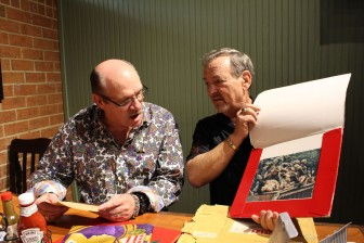 "From left, Richard Hill reacts as Alvin ""A.B."" Grantham shows him an iconic photo from the Vietnam War that features both men."