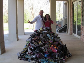 (Photo | Submitted) Dr. John Todd and Rachael Hartman of Baldwin Bone & Joint display the mountain of shoes collected during the 2016 Many More Miles Campaign. The 1,899 pairs of shoes were donated to the outreach programs of Wings of Life and Discovery Ministries.