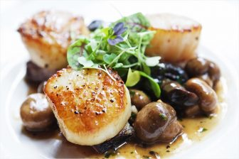 (Photo | Dan Anderson/Lagniappe) Dumbwaiter's pan-seared scallops include garlic-braised mushrooms, small-batch bacon and a Good People Brown Ale reduction.