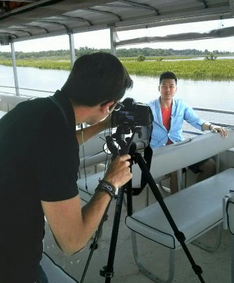 Brand USA videographer Bogdan Zlatkov records Brand USA on-camera host, Vic Liang on a boat trip at Five Rivers Delta Resource Center in Spanish Fort.  (Brand USA photo)