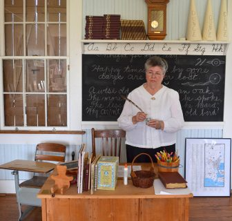 (Photo | Jo Anne McKnight) Semmes Heritage Day chairperson Jeanette Byrd with some of the artifacts in the 1902 Semmes School.