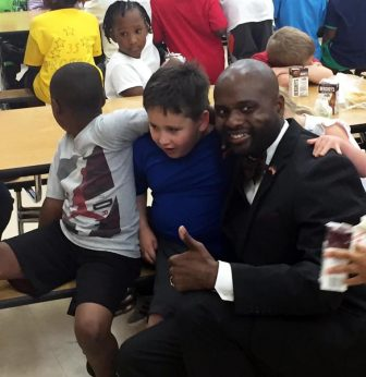 Councilman C.J. Small greets student at Gilliard Elementary on Monday, after he returned home from South Africa. He was shot in the face after the tour bus he was riding in was ambushed in a suburb of Johannesburg.