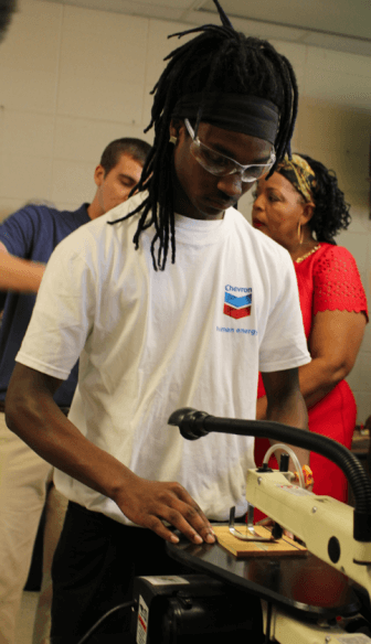A member of the Williamson High School robotics team uses a ban saw donated by Chevron. (Jason Johnson)